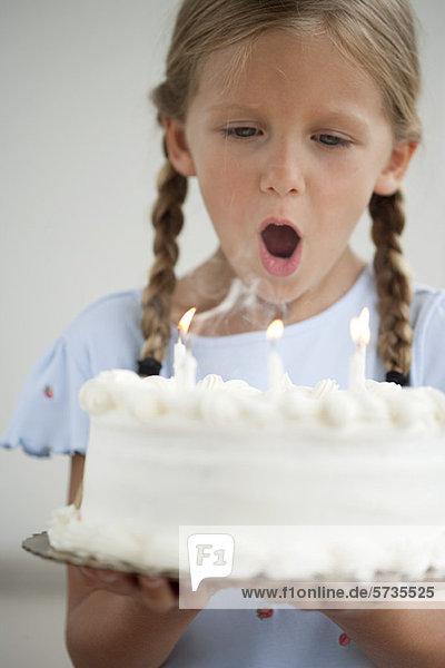 Mädchen beim Ausblasen von Kerzen auf Geburtstagskuchen