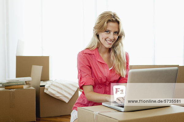 Young woman using laptop computer while surrounded by cardboard boxes