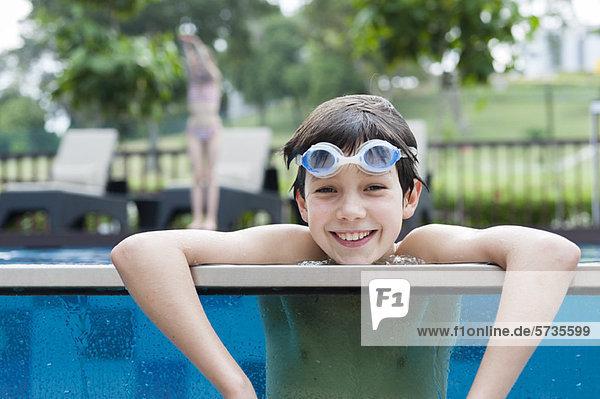 Junge mit Schutzbrille am Beckenrand  lächelnd  Portrait