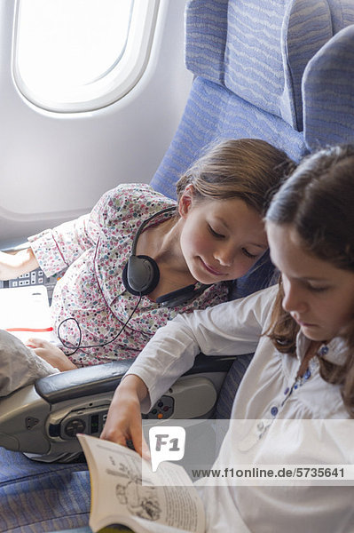 Girl on airplane leaning over to look at older sister's book