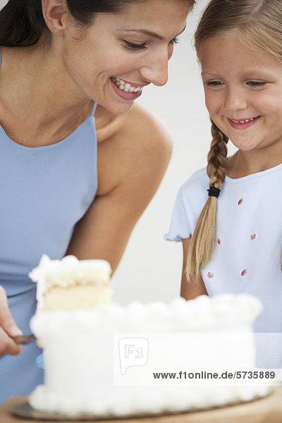 Mutter und Tochter beim Kuchenschneiden