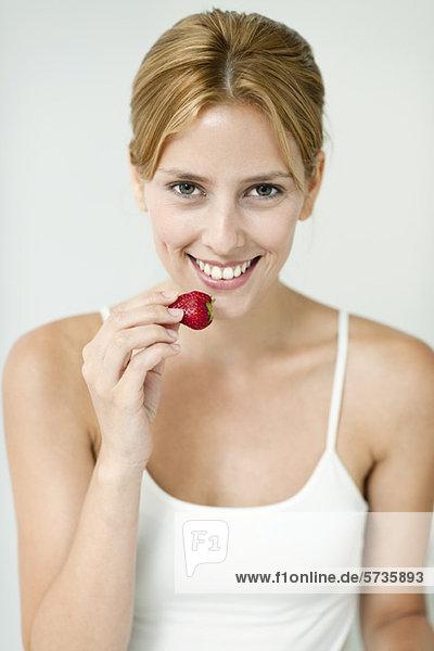 Junge Frau isst Erdbeere  Portrait
