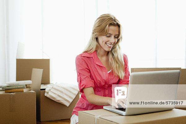 Junge Frau  die einen Laptop benutzt  während sie von Pappkartons umgeben ist.