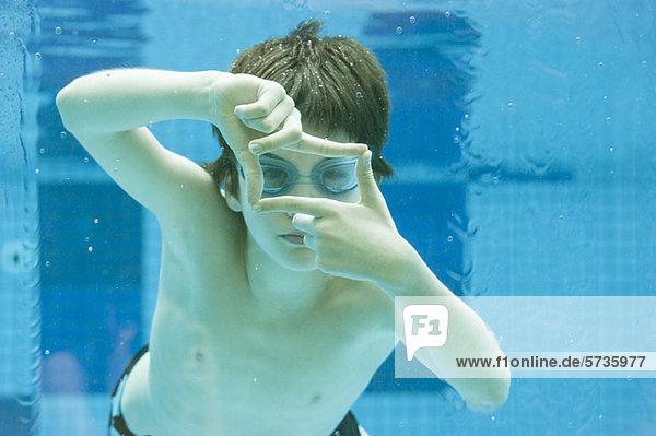 Junge schwimmt unter Wasser im Schwimmbad  Hände bilden Fingerrahmen