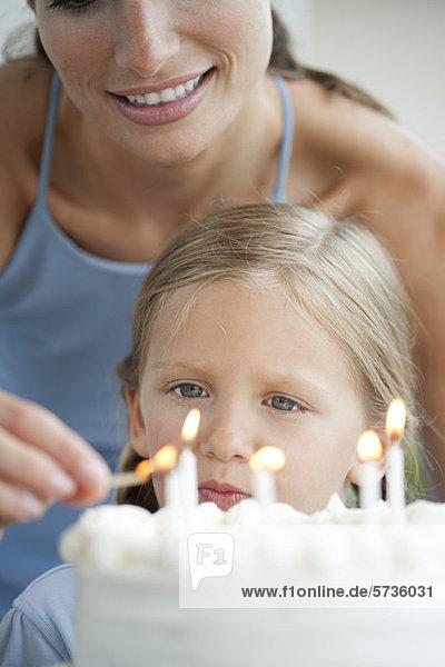 Mädchen sieht zu  wie ihre Mutter Kerzen auf dem Geburtstagskuchen anzündet.