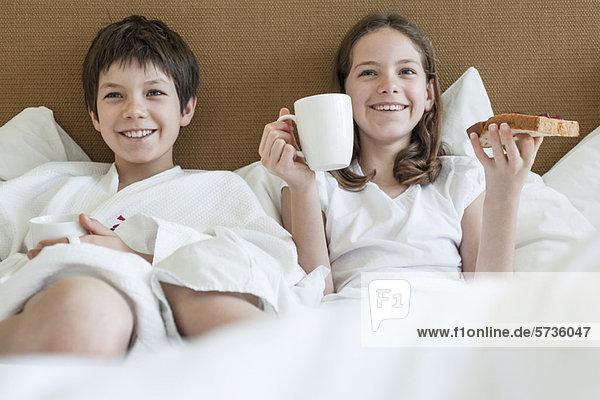 Bruder und Schwester liegen im Bett und frühstücken.
