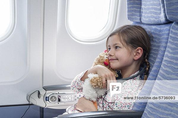 Mädchen umarmt Plüschtier im Flugzeug