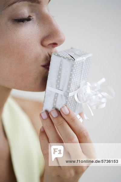 Frau küssend verpacktes Geschenk  Augen geschlossen