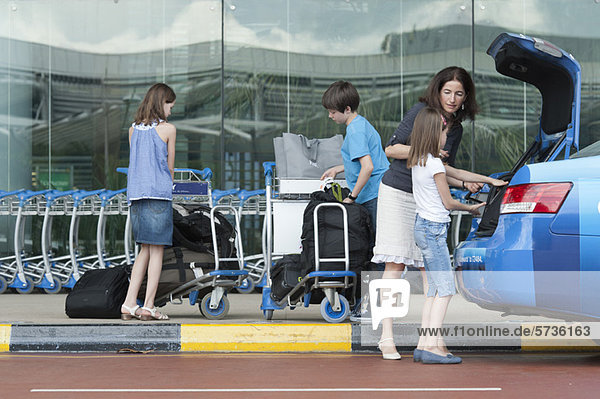 Familie außerhalb des Flughafens beim Entladen des Gepäcks aus dem Taxistamm