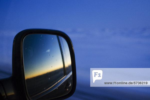 Sonnenuntergang im Seitenspiegel des Autos reflektiert