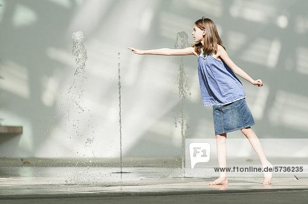 Mädchen  das nach dem vertikalen Wasserstrahl greift  der aus dem öffentlichen Brunnen steigt.