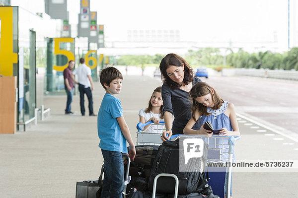 Familie steht vor dem Flughafen mit Gepäck