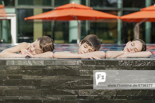 Geschwister  die sich am Rand des Schwimmbeckens nebeneinander lehnen  Köpfe auf den Armen liegend