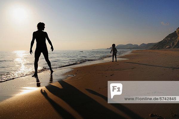 Mann und Kind am Strand