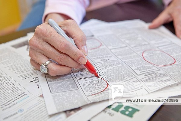 Woman circling employment ads in paper