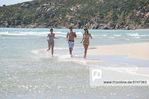 Freunde rennen in Wellen am Strand