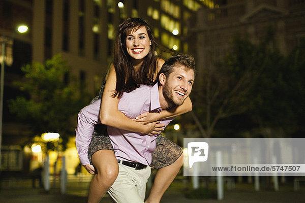 Man carrying girlfriend on city street