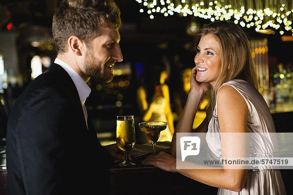 Lächelndes Paar bei einem Drink an der Bar