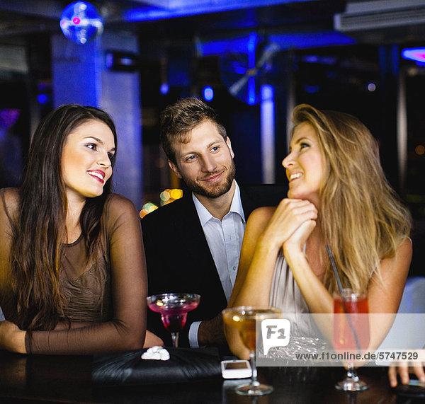 Mann im Gespräch mit Frauen in der Bar
