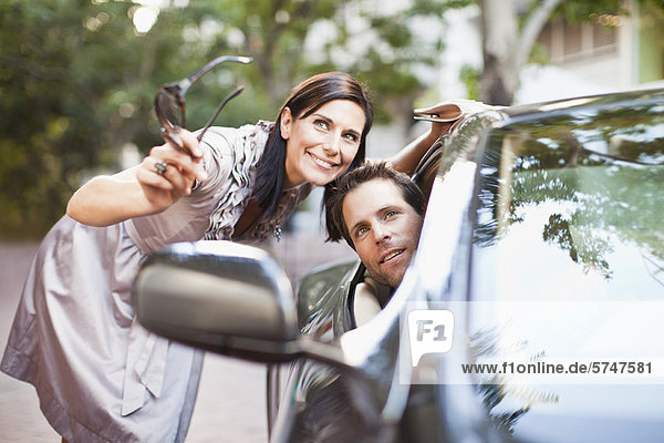 Woman giving directions to man in car