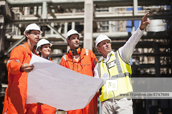 Arbeiter mit Blaupausen in der Ölraffinerie