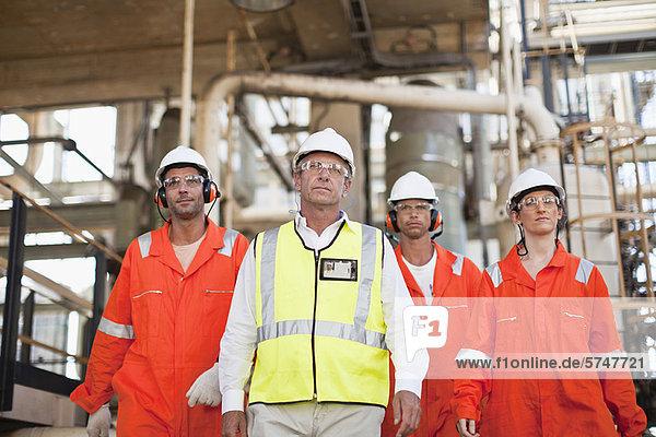 Arbeiter  die in der Ölraffinerie spazieren gehen