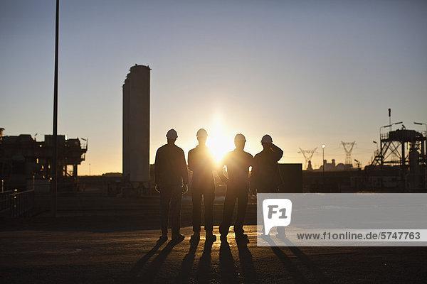 Silhouette der Arbeiter in der Ölraffinerie