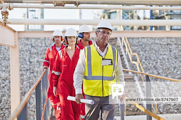Arbeiter  die in einer Chemiefabrik spazieren gehen