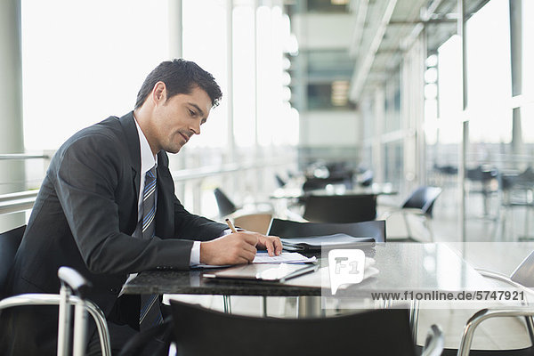 Businessman making notes in cafe