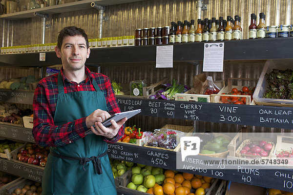 Lebensmittelhändler mit Tablet-Computer im Geschäft