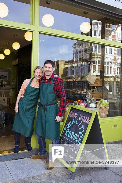 Lächelnde Lebensmittelhändler stehen vor dem Laden