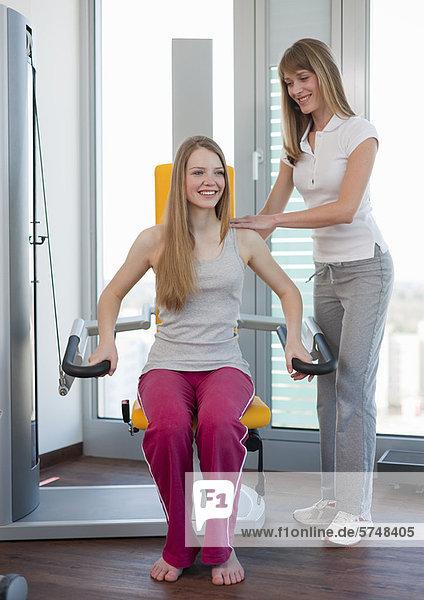 Trainerin bei der Arbeit mit Mädchen im Fitnessstudio