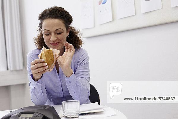 Geschäftsfrau beim Essen am Schreibtisch im Büro