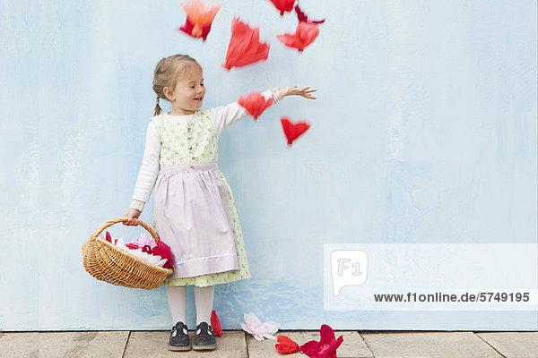 Lächelndes Mädchen spielt mit Papierblumen