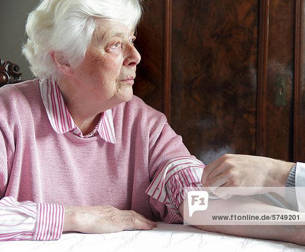 Ältere Frau mit Pulskontrolle