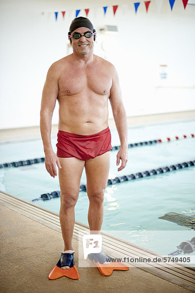 Mann in Schwimmbekleidung am Pool