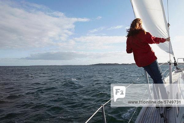 Frau segelt auf der Yacht  Rückansicht