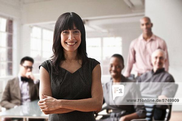Portrait einer Geschäftsfrau mit Kollegen im Hintergrund