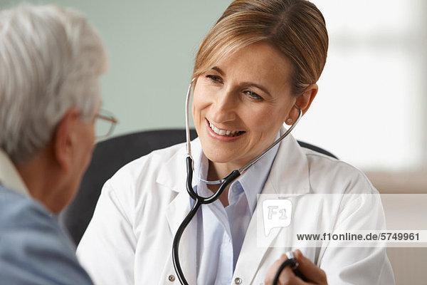 Arzt  der den Blutdruck des älteren Mannes nimmt.