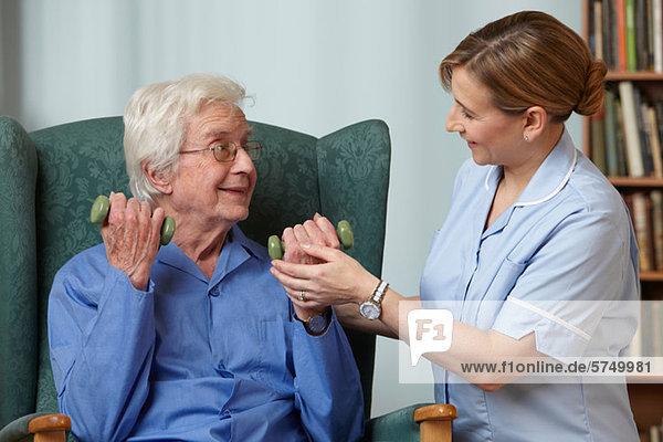 Betreuerin mit Handgewichten für Senioren