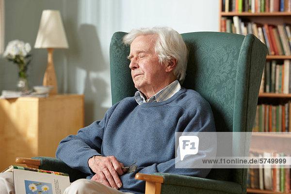 Senior im Sessel schlafend