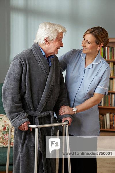 Betreuerin  die den älteren Mann mit einem Gehgestell unterstützt