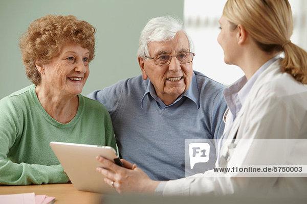 Arzt mit digitalem Tablett und Seniorenpaar