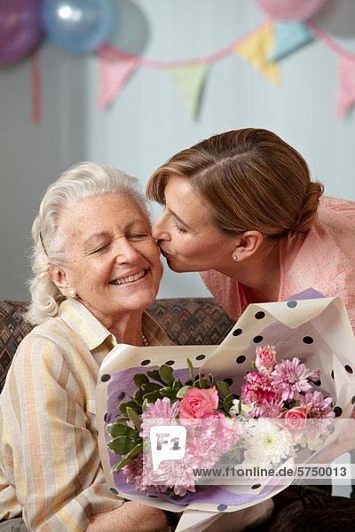 Tochter schenkt Senior-Mutter Blumenstrauß