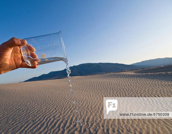 Mann gießt Wasser aus Becherglas im Death Valley National Park  Kalifornien  USA