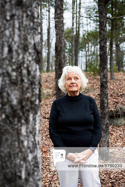 Porträt einer älteren Frau im Wald  Hände umklammert