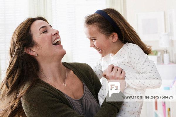 Mittlere erwachsene Frau mit Tochter  lächelnd