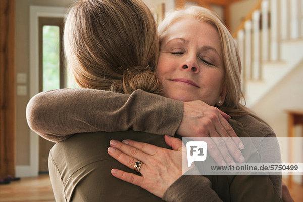 Mutter umarmt erwachsene Tochter