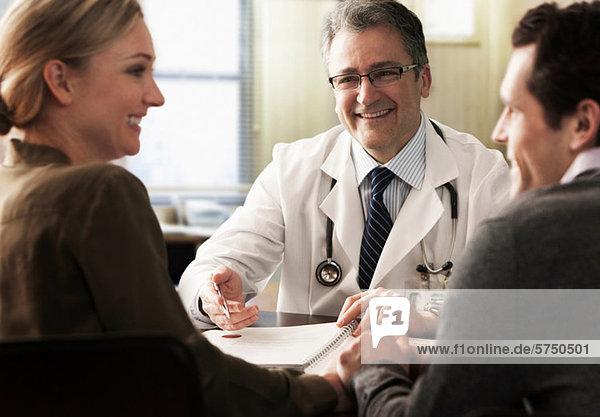 Junges Paar in Arztpraxis erhält gute Nachrichten