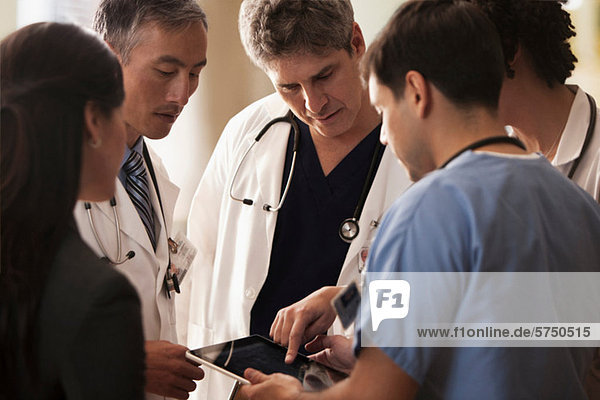 Doctors discussing patients charts on digital tablet in hospital